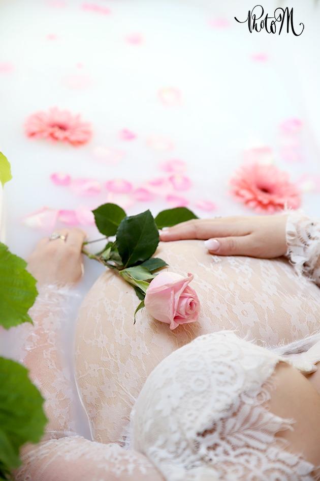ventre rond d'une femme enceinte dans bain de lait avec rose