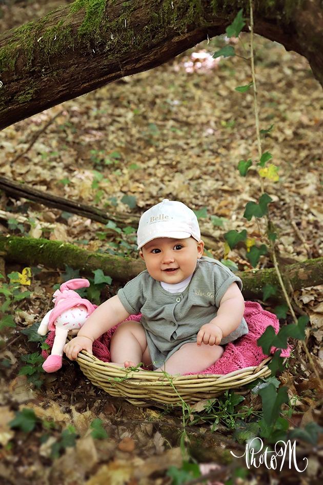 fillette dans panier et sur tapis de feuilles dans la forêt