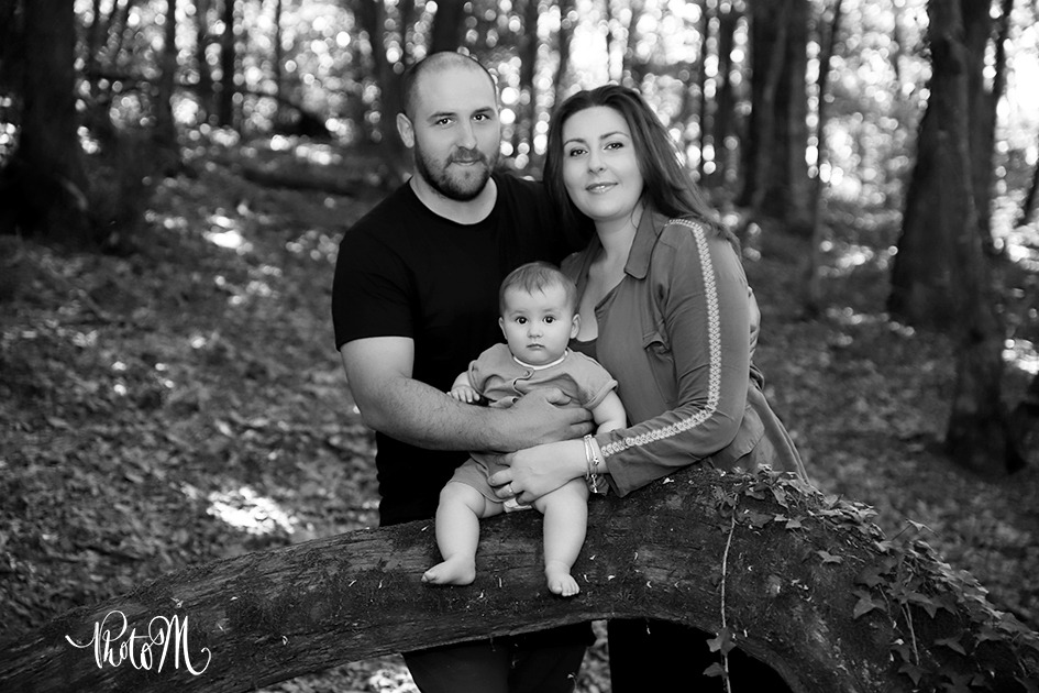 belle famille avec fillette assise sur un tronc d'arbre