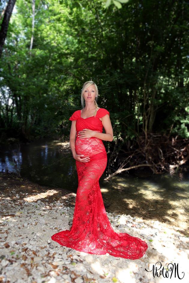 photo de grossesse au bord d'un ruisseau robe en dentelle rouge