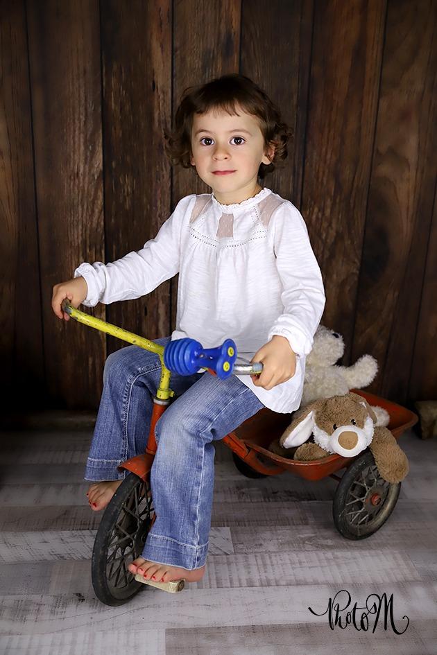 Portait fille sur vélo avec peluches